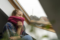 Happy young woman with scarf at the window - GUSF02020
