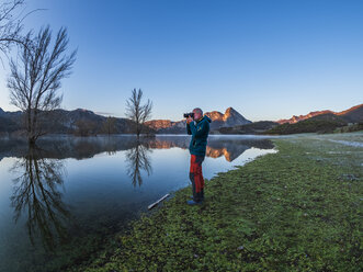 Spain, Asturias, Camposolillo, Cantabrian Mountains, senior man taking a photo at the seashore of Porma reservoir - LAF02326