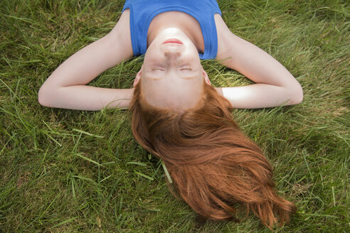 Caucasian girl laying in grass with hands behind head - BLEF03442