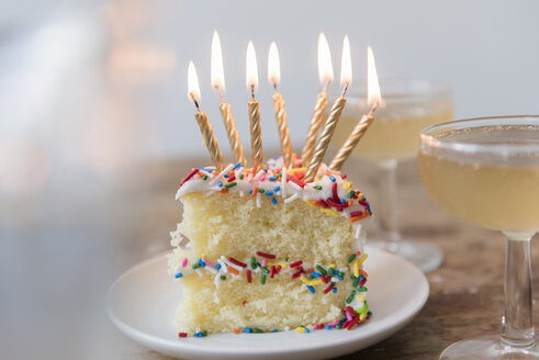 Candles burning on slice of cake with sprinkles near champagne - BLEF03448