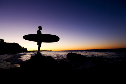 Silhouette of Hispanic man holding surfboard at beach - BLEF03472