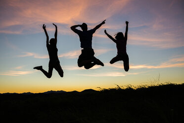 Silhouette of friends jumping for joy at sunset - BLEF03475
