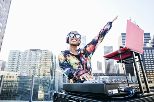 Smiling Black DJ on urban rooftop - BLEF03508