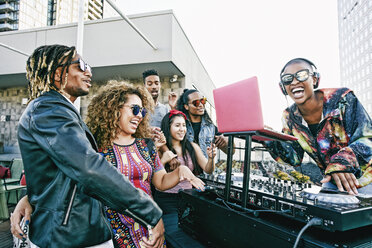 Friends smiling with DJ on urban rooftop - BLEF03511