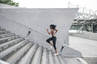 Mixed Race woman running up urban staircase - BLEF03559