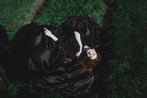 Caucasian woman wearing black dress sleeping on grass - BLEF03574