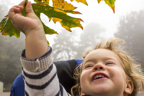 Smiling Caucasian girl holding autumn leaf - BLEF03622