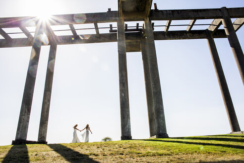 Caucasian brides holding hands walking under concrete structure - BLEF03628