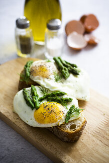 Slices of baguette garnished with fried eggs and Asparagus on a plate - GIOF06328