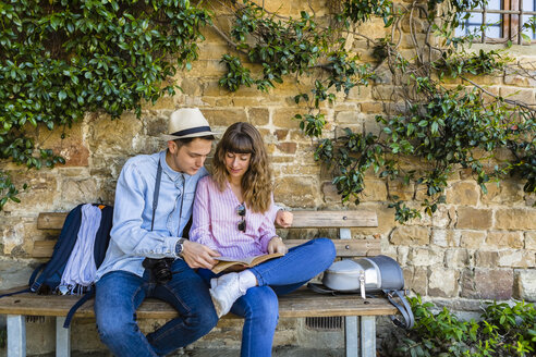 Young couple on a city break, sitting on a bench, reading guidebook - MGIF00419
