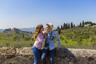 Young couple embracing at wall in Florence, Tuscany, Italy - MGIF00434