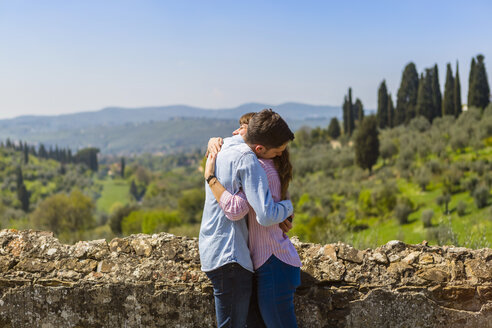 Young couple embracing at wall in Florence, Tuscany, Italy - MGIF00440