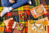 Young woman having a picnic with healthy food in a park - MGIF00452