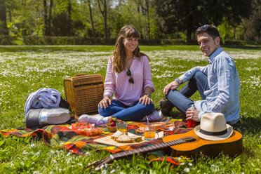 Young couple having a picnic with healthy food in a park - MGIF00455