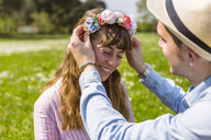 Young man putting flowers on on his girlfriend's head - MGIF00464