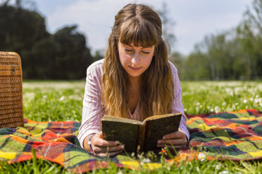 Young woman lying on a picnic blanket, reading a book in a park - MGIF00470