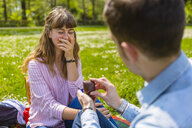 Young man proposing to his girlfriend in a park - MGIF00473