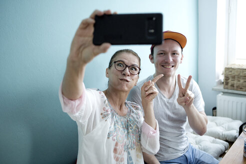 Mother and son sitting at the kitchen table, taking smarrtphone selfies - FLLF00143