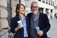 Portrait of smiling mature couple with reusable bamboo cups in the city - ECPF00744