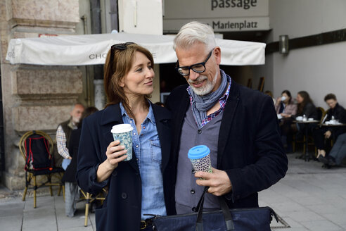 Smiling mature couple with reusable bamboo cups in the city - ECPF00747