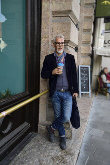Mature man with reusable bamboo cup standing in the city - ECPF00753
