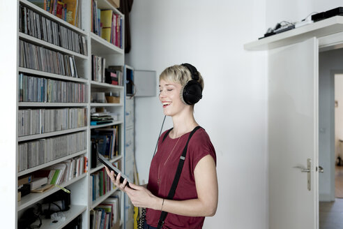 Happy woman listening to music with headphones at home - FLLF00145