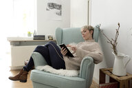 Relaxed woman sitting in armchair at home using tablet - FLLF00157