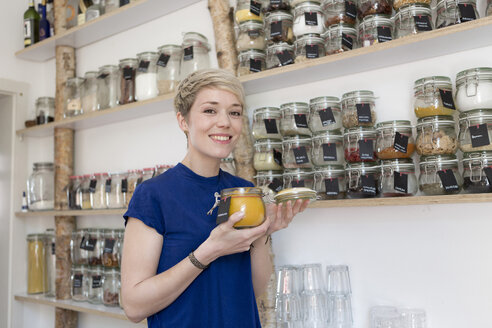 Portrait of smiling woman holding jar in front of spice shelf in kitchen - FLLF00169
