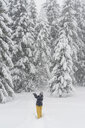 Finland, Kuopio, woman catching snowflakes in winter forest - PSIF00261