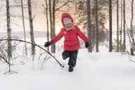 Finland, Kuopio, happy toddler girl running in winter landscape at sunset - PSIF00264