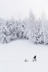 Finland, Kuopio, mother and daughter with sledge in winter forest - PSIF00267