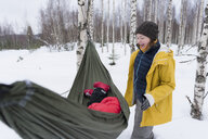 Finland, Kuopio, mother with daughter in hammock in winter landscape - PSIF00273