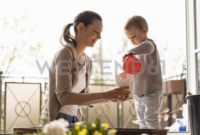 Mother and daughter planting flowers together on balcony - DIGF07032 - Daniel Ingold/Westend61
