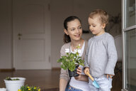 Mother and daughter planting flowers together at home - DIGF07044