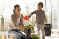 Mother and daughter planting flowers together on balcony - DIGF07050