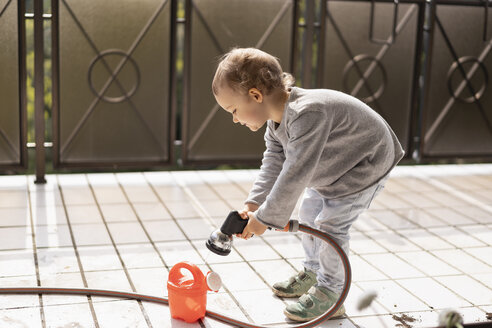 Cutle little girl filling water into watering can - DIGF07053