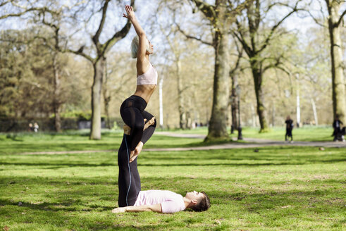 UK, London, Greater London. Young couple doing yoga acrobatics in an urban park. Sport concept. - JSMF01076