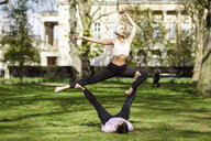 Young couple doing yoga acrobatics in an urban park - JSMF01079