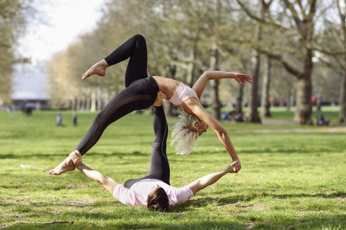 Young couple doing yoga acrobatics in an urban park - JSMF01082