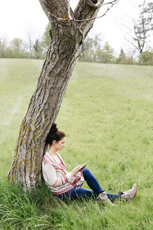 pretty, young woman with black hair sitting in a green meadow, leaning against a tree and working with her tablet, lower austria, austria - HMEF00370
