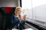 Smiling blond woman travelling by train using smartphone and earphones - HMEF00375