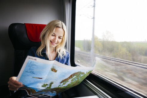 Portrait of happy blond woman travelling by train looking at map of Europe - HMEF00381