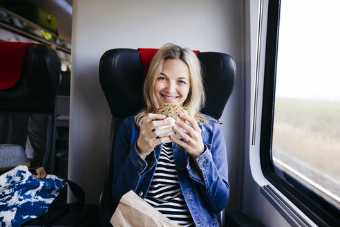 Portrait of smiling blond woman travelling by train having a snack - HMEF00384