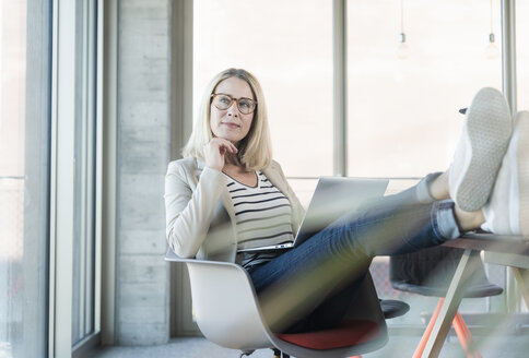 Relaxed businesswoman using laptop in office with feet up - UUF17464