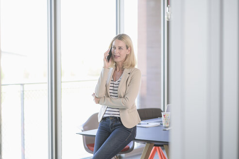 Businesswoman talking on cell phone in office - UUF17476