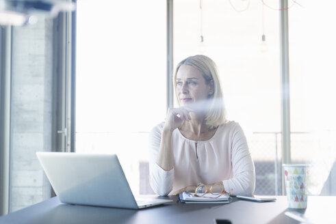 Businesswoman using laptop in office - UUF17494