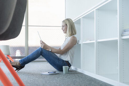 Casual businesswoman sitting on the floor in office using tablet - UUF17500