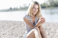 Portrait of happy mature woman sitting at the riverside - UUF17584