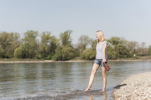Carefree mature woman splashing in a river - UUF17590