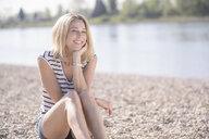 Smiling mature woman sitting at the riverside - UUF17593